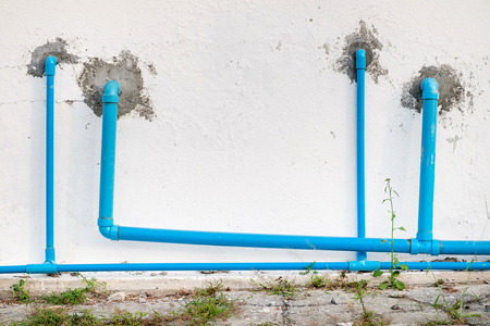 old blue pipe on white wall