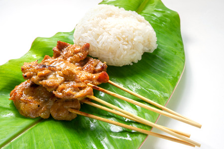 local Thai popular food - grilled pork with sticky rice on banana leaf