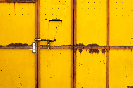 vintage yellow metal fence with rusty door Фото со стока