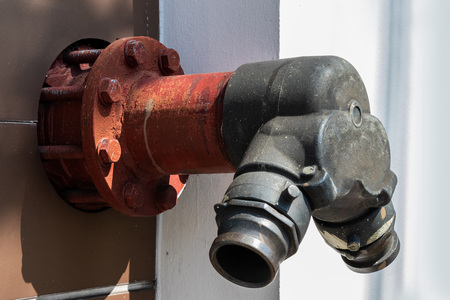 red fire pump hydrant on the wall. public fire pipeline on sidewalk - fire safety or water supply valve, High pressure