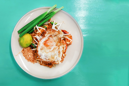 fried egg on top of padthai with shrimps
