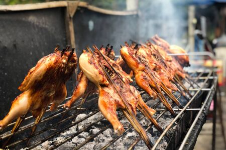 asian street food - grilled chickens on the grill pan close-up