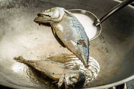 selective focus on mackerel fish on stainless steel turner for frying in pan with hot cooking oil Stock Photo