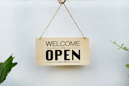 welcome we're open. black text on wood sign hanging on white wall hanve plant in forground Standard-Bild