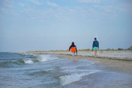 A guy and a girl are walking in the distance. An azure sea wave with a white crest runs ashore.