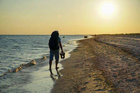 a guy with a backpack walks along the coastline in the evening barefoot on the sand, holds sandals in his hand