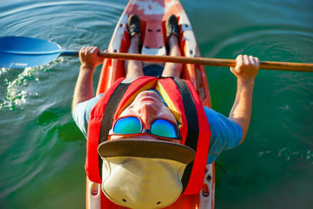 the guy swims on a red canoe in glasses and a cap. Top view