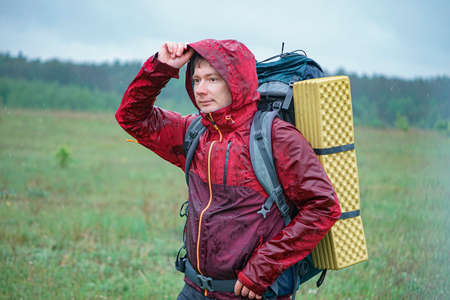 Hiker with a large backpack getting wet in the rain while traveling in the mountains
