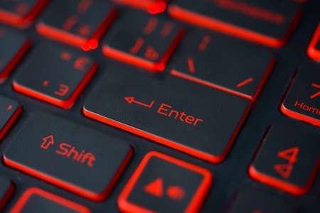 Red backlit computer keyboard macro shot of enter key