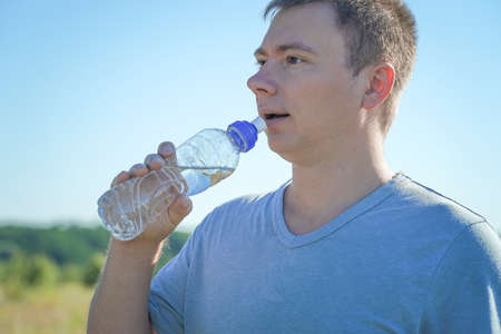 a guy with glasses and a t-shirt holds a plastic water bottle in his hands