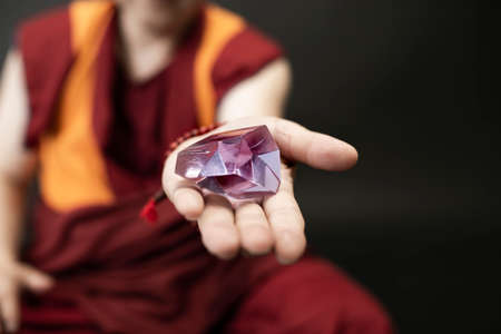 Buddhist monk in red kesa, holding a crystal of glass in his hand