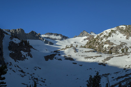 pct: Sierra Sunlight - Sunlight across a snowy Sierra Nevada mountain face on the pacific crest trail.