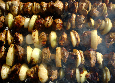 Grilling shashlik with bow is cooked on fire. Grilled meat.