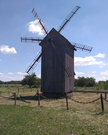 Old wooden windmill stands in the field among the grass