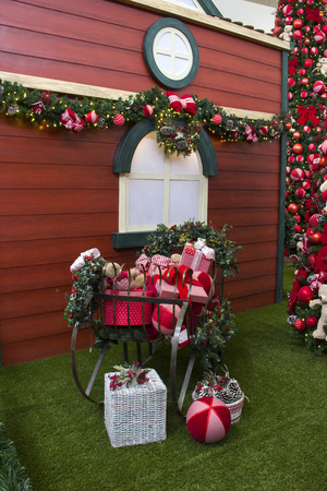 decorated tree: Christmas gifts inside sleigh, with flowers and decorated tree
