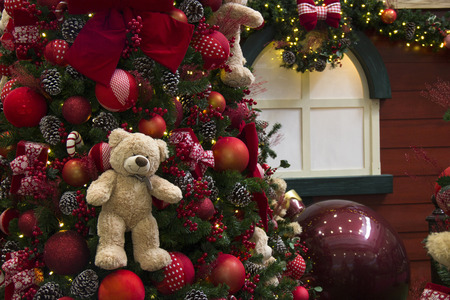 festooned: Christmas decoration, tree festooned with balls, lights, gifts and bears. House decorated in the background
