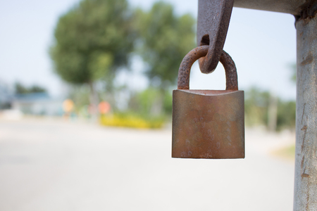 Gold Padlock with chain used on a chainlink fence. Selective focus is use on the padlock. Stock Photo