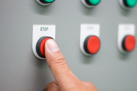 """A mão pressionando o interruptor """"STOP"""" no painel de controle"""