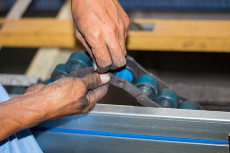 The technician repairing conveyor belt in factory