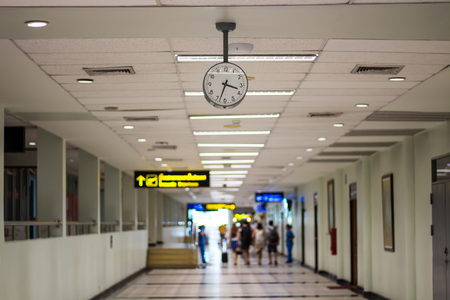 Picture for your concept Time clock inside the airport building And people traveling (blurred images)
