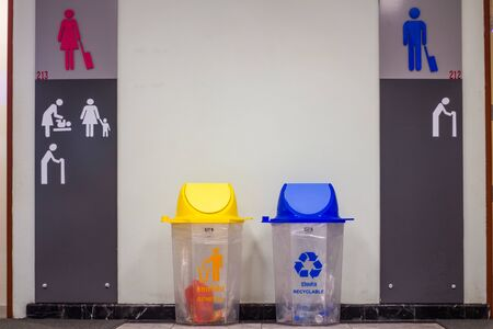Picture for your concept  yellow trash is general waste and blue is recyclable waste in front of the bathroom inside the airport building.