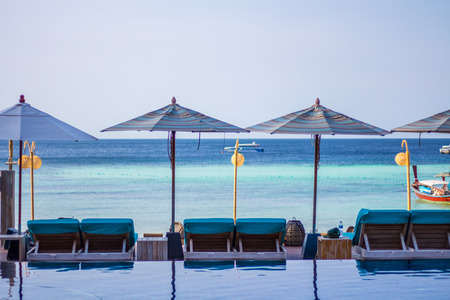 Beach and sea swimming pool With umbrellas and sun loungers At the island in Thailand