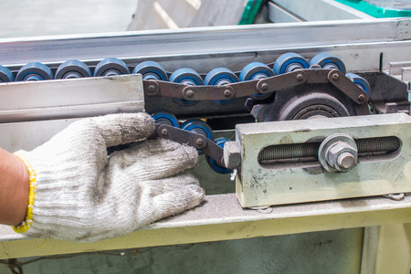 The hand of technician checking strength and tension of conveyor belt for maintenance Stock fotó