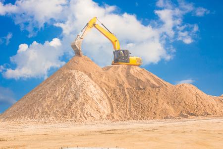 Excavators work on soil piles for construction.