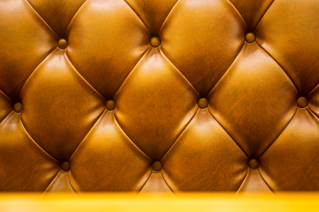 The brown soft leatherette background with asymmetrical buttons. Soft and expensive furniture elements. Luxury background