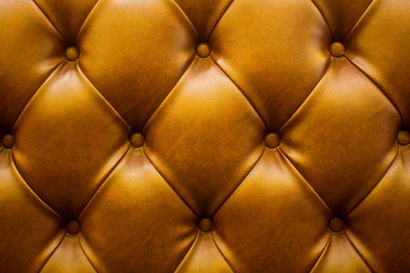 Der braune weiche Kunstlederhintergrund mit asymmetrischen Knöpfen. Weiche und teure Möbelelemente. Luxus-Hintergrund Standard-Bild