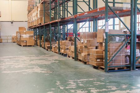 The rows of shelves with boxes in warehouse. Stock Photo