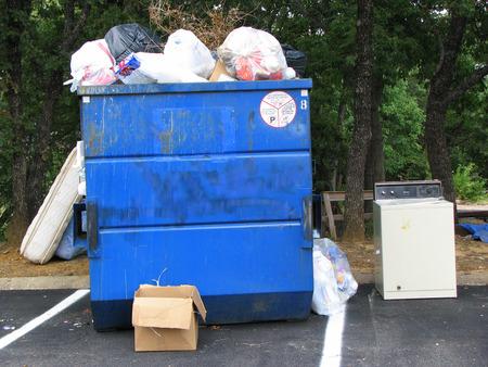hazardous waste: Blue Garbage Dumpster filled over the top