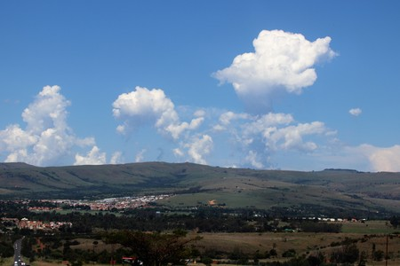 Tranquil scenery with hills, clouds and a small town Imagens