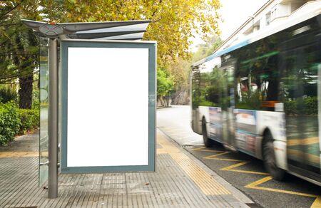 Tabellone per le affissioni verticale vuoto bianco alla fermata dell'autobus sulla strada della città. Sullo sfondo di autobus e strade. Schizzo. Poster sulla strada accanto alla strada.
