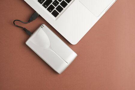 Aluminum external hard drive, partial laptop view, brown background, office concept. Imagens
