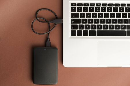 black external hard drive, partial laptop view, brown background, office concept.top view Imagens