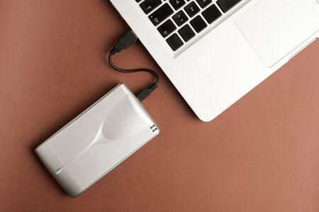 Aluminum external hard drive, partial laptop view, brown background, office concept. Zdjęcie Seryjne