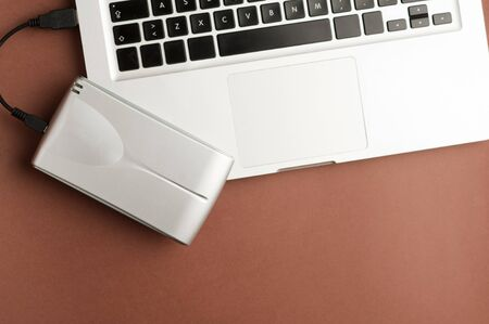 Aluminum external hard drive, on top of laptop, brown background, office concept.top view Zdjęcie Seryjne