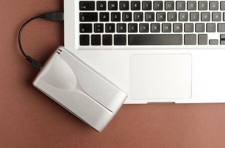 Aluminum external hard drive, on top of laptop, brown background, office concept.top view Imagens