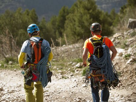 Two climbers, senior man and young man, with ropes, and climbing equipment run across the field, rock mountain climbing team