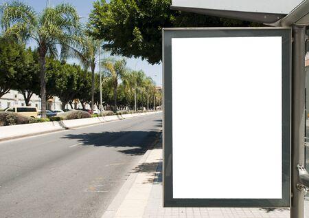 Panneau d'affichage vertical blanc à l'arrêt de bus dans la rue de la ville. En arrière-plan des bus et des routes. Esquisser. Affiche dans la rue à côté de la route.