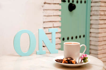 activate concept, (letters ON) cup of coffee with sweet, on marble table, with pastries in wicker basket, and background of Mediterranean house, space for text