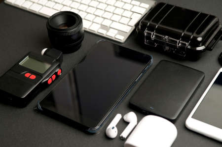 photography accessories group, with black electronic phonebook, photometer, photographic lens, white computer keyboard, headphones, waterproof case, black hard drive, and telephone, on black table