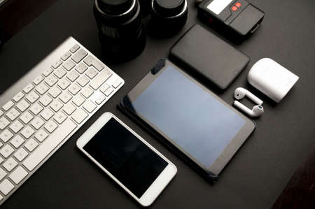 group accessories table work photographer, with white computer keyboard, white telephone, black electronic phonebook, two lenses, hard disk, photometer, white headphones with white box, on black backg