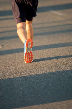 runner with black clothes and blue shoes with orange sole and gray detail left leg in the air