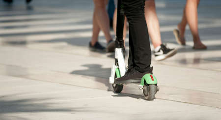 white and green electric scooter, in the street, with boy's legs, black pants and sports shoes Stockfoto