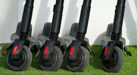 group of black electric scooters, on grass