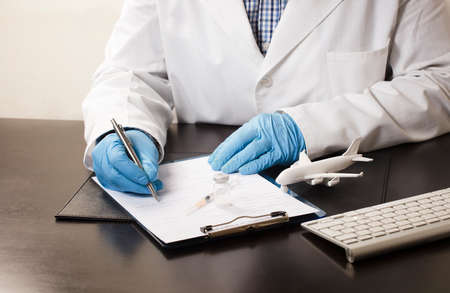 Doctor's hand with pen filling in data, on form, with vaccine, syringe, white plane, computer keyboard, on work table, white background. Stock Photo