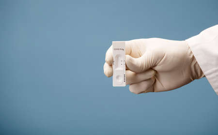 Doctor holding a test kit for viral disease tests with the COVID-19 SARS-CoV-2 laboratory card kit for the novel viral coronavirus sars cov 2 virus (formerly known as 2019-nCov)