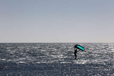 Man practicing with wing-surfer at sunset in the sea